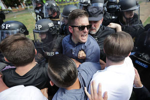 White man in blue shirt surrounded by White men in multicolored clothes and White police officers in black riot gear in front of green grass