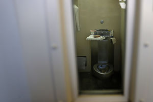 A narrow, beige death row cell with a tray of food sitting on the sink
