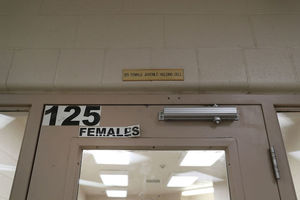 Brown door with white signs with black text under light brown ceiling