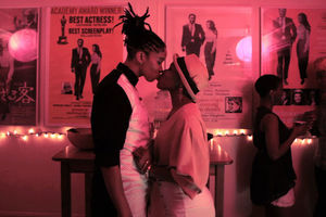 Black woman with dreadlocks and black-and-white shirt kisses Black woman in brown hat and dress in room with pink light and posters with black text and images