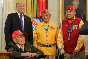 Brown men in green and yellow and red military regalia with blue ceremonial jewelry stand and sit near White man in black suit with purple tie in front of yellow and brown wall with red and yellow and green flags and red and white and blue banner