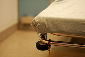 Hospital bed with chain on railing