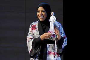 Black woman in black hijab and white outfit with black and pink details holding Black doll with white clothing in front of dark grey background