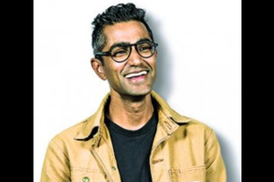 Brown man in light brown jacket and black t-shirt on white background