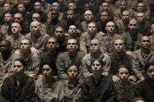 Black and Brown and White women and men in dark green military fatigues sitting in rows behind dark brown wall
