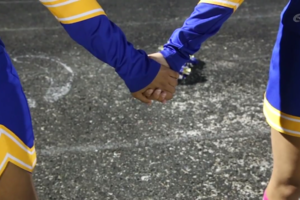 Cheerleaders hold hands