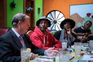 U.S. Senate candidate Doug Jones, wearing a suit, sits at a table with a Black man in a fisherman's hat, a Black woman in a black wool hat and a Black man wearing a black and black khaki striped shirt