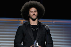 Black man in black suit with black afro holds glass award statue behind black microphone and in front of black and grey background