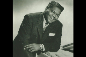 Black-and-white image of Black man in dark suit with patterned tie on piano in front of grey background