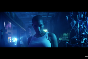 A Black woman with a shaved head wearing a white tank top stares piercingly into the camera as she stands in a room awash with blue lighting.
