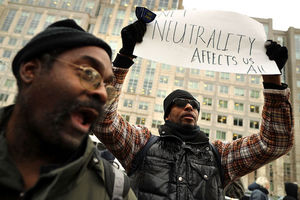 "A black man wearing a black vest holds up a sign that says ""Net neutrality affects us all."""