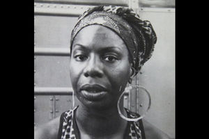 Black-and-white image of Black woman in patterned head wrap with hoop earrings and patterned halter top in front of grey background