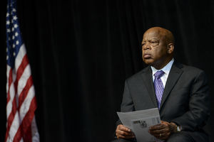 Black man in dark grey suit with purple tie and light blue shirt holds white papers with black text in front of black background and red and white and blue U.S. flag