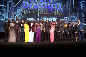 Black women and men and White men in multicolored clothing on black stage in front of dark screen with blue and white text