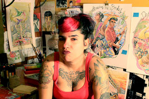 Photo of the artist, Latina woman with tattoos and black hair posing in her studio with artwork behind her