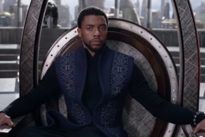 Black man in grey and black outfit sitting on black throne in front of red and brown background
