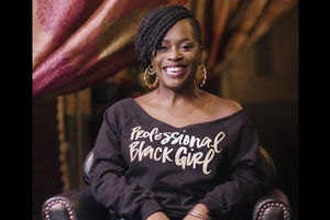Black woman in black shirt with gold lettering smiles while sitting on brown chair in front of blurry black and red background