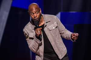 Black man in black t-shirt and grey jacket holds black microphone in front of black and blue and grey background
