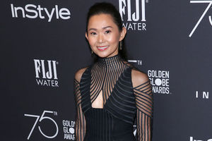 Asian woman in black dress stands and smiles in front of dark grey wall with white text and logos