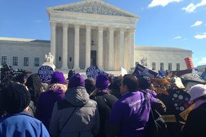 A crowd of people stands before the Supreme Court building.