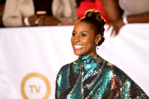 Black woman in green dress and eye makeup smiles in front of white wall with gold text and Black people in multicolored clothing