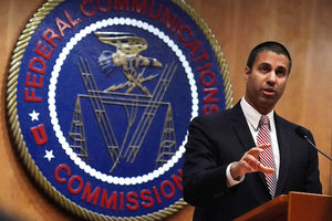 Brown man in navy suit with red and white striped tie speaks behind brown podium and black microphone in front of brown wall with blue and gold seal with white and gold details and red text