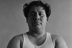 Black-and-white photo of Brown man with black hair in white tank top in front of grey wall