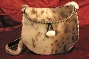 Brown purse with brown spots and white ivory bead on black string in front of red felt background