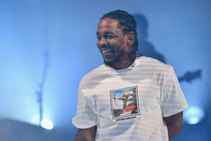 Black man with black cornrows smiles while wearing white t-shirt with multicolored logo and black text in front of blue background
