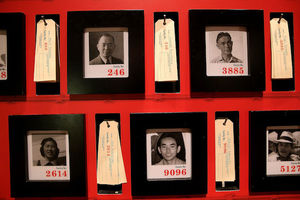 Asian woman and men in black-and-white photos framed by white and black frames on red wall with brown identification tags