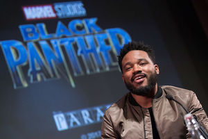 "Ryan Coogler. Black man sits on a stage in a tan bomber jacket, with ""Black Panther"" projected on the screen behind him"