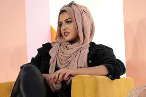 Brown woman in pink hijab and black jacket and pants holds black microphone while sitting on yellow chair in front of pink and yellow and white wall