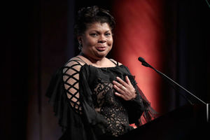 April Ryan. Black woman in black dress on stage behind a podium, smiles to camera.