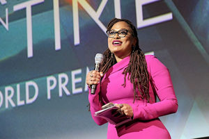 Black woman with brown hair in pink dress and black glasses smiles while holding black microphone and grey paper in front of blue and green screen with white text
