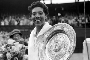 Black-and-white photograph of Black woman in white tennis jacket next to metal award plate and flowers in front of woman in grey hat and grey audience