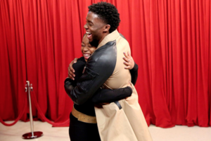 Black woman in black dress with black belt smiles and hugs Black man in brown and black jacket in front of red curtain and brown floor