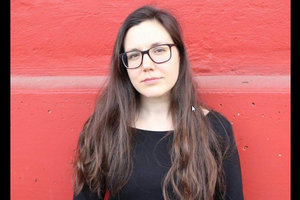 Brown woman with brown hair in black shirt and brown glasses stands in front of red wall