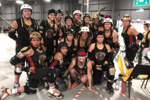 Native women in roller derby gear gather in a group photo