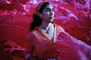 Infrared image of Brown woman in orange and pink shirt and bandana and blue pants surrounded by pink vegetation in front of grey sky.