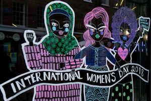 "Colorful line drawing on glass window depicts three women with banner that reads, ""International Women's Day 2018"""