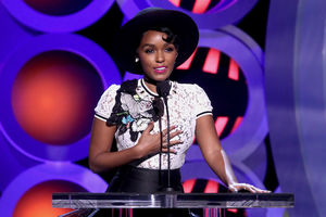 Black woman in black hat and white blouse with black and yellow ornament and black skirt and pink lipstick smiles behind black microphone and podium in front of blue and orange and black and pink background