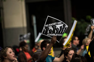"""Protesters in street, one sign reads, """"No racist USA, #Charlottesville."""""""