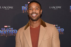 Black man in red sweater and brown coat in front of black wall with blue and white text