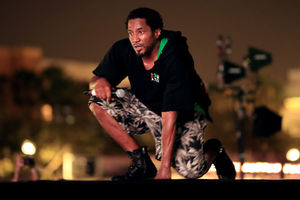 Black man in black sweatshirt and green and brown camouflage shorts kneels on black stage in front of brown sky