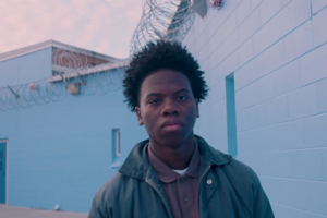 Black boy with brown skin looks at camera while standing in front of high blue walls laced with barbed wire