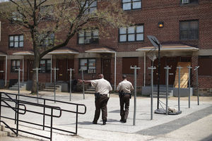 Two police officers walking towards a public housing apartment complex