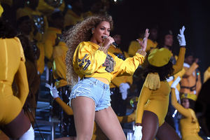 Black woman with blonde hair in gold windbreaker with black and pink and gold and silver logos and embroidery and blue denim shorts stands next to Black women and men in yellow outfits on grey risers in front of black background