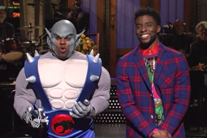 Black man in grey prosthetic makeup and blue and white and grey costume next to Black man in multicolored shirt under red and blue plaid blazer in front of brown doors and band in black clothing