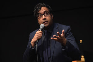 Brown man in black glasses and navy suit holding black microphone in front of black background