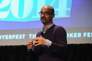 Junot Díaz. Brown man in deep purple sweater, blue and white striped button down and black-rimmed glasses stands and talks in front of a screen